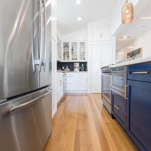 Small coastal eat-in kitchen remodeling - Inspiration for a small coastal galley medium tone wood floor eat-in kitchen remodel in Miami with recessed-panel cabinets, blue cabinets, marble countertops, stainless steel appliances and no island
