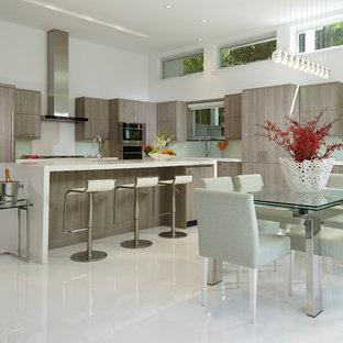マイアミの大きいコンテンポラリースタイルのおしゃれなキッチン (ドロップインシンク、フラットパネル扉のキャビネット、グレーのキャビネット、クオーツストーンカウンター、緑のキッチンパネル、ガラス板のキッチンパネル、シルバーの調理設備の、大理石の床) の写真