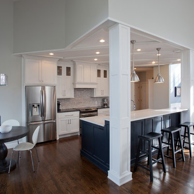 Mid-sized transitional galley dark wood floor and brown floor open concept kitchen photo in St Louis with shaker cabinets, white cabinets, laminate countertops, white backsplash, stainless steel appliances, an island, porcelain backsplash and a farmhouse sink