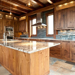 This is an example of a large country l-shaped open plan kitchen in Denver with an undermount sink, shaker cabinets, medium wood cabinets, granite benchtops, blue splashback, glass tile splashback, stainless steel appliances, slate floors, with island, multi-coloured floor and multi-coloured benchtop.