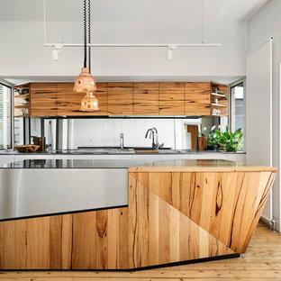 Diseño de cocina en L, actual, con fregadero bajoencimera, armarios con paneles lisos, puertas de armario de madera oscura, salpicadero con efecto espejo, electrodomésticos negros, suelo de madera clara, una isla y encimeras multicolor