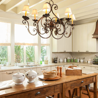 Kitchen - small beach style l-shaped medium tone wood floor kitchen idea in Charleston with a double-bowl sink, recessed-panel cabinets, beige cabinets and an island