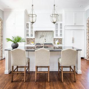 Создайте стильный интерьер: параллельная кухня в классическом стиле с врезной раковиной, фасадами с утопленной филенкой, белыми фасадами, коричневым фартуком, фартуком из кирпича, техникой под мебельный фасад, темным паркетным полом, островом и коричневым полом - последний тренд