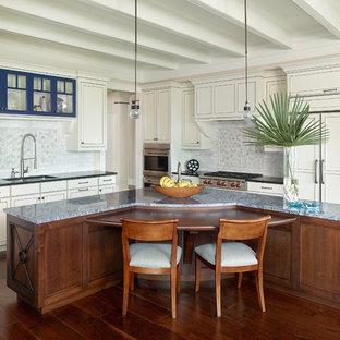 チャールストンの中サイズのビーチスタイルのおしゃれなアイランドキッチン (アンダーカウンターシンク、白いキャビネット、御影石カウンター、白いキッチンパネル、セラミックタイルのキッチンパネル、落し込みパネル扉のキャビネット、パネルと同色の調理設備、無垢フローリング、オレンジの床) の写真