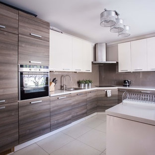 This is an example of a medium sized modern single-wall kitchen/diner in Las Vegas with flat-panel cabinets, white cabinets, laminate countertops, white splashback, plywood flooring, an island, beige floors and white worktops.