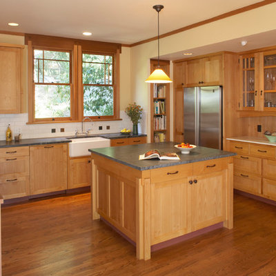 Example of an arts and crafts l-shaped kitchen design in San Francisco with a farmhouse sink, shaker cabinets, medium tone wood cabinets, beige backsplash, subway tile backsplash and stainless steel appliances