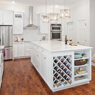 Inspiration för mellanstora klassiska kök, med en rustik diskho, luckor med infälld panel, vita skåp, bänkskiva i kvarts, vitt stänkskydd, stänkskydd i keramik, rostfria vitvaror, mellanmörkt trägolv, en köksö och brunt golv