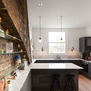 Photo of a medium sized contemporary kitchen in London with a submerged sink, flat-panel cabinets, black cabinets, marble worktops, light hardwood flooring, a breakfast bar and beige floors.