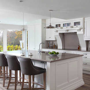 Example of a large classic single-wall medium tone wood floor and brown floor open concept kitchen design in Other with an integrated sink, beaded inset cabinets, white cabinets, quartzite countertops, brown backsplash, stone slab backsplash, stainless steel appliances and an island