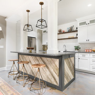 Inspiration for a medium sized urban l-shaped open plan kitchen in Chicago with a double-bowl sink, shaker cabinets, white cabinets, granite worktops, white splashback, metro tiled splashback, stainless steel appliances, cement flooring and an island.