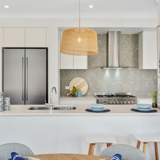 Design ideas for a beach style galley eat-in kitchen in Brisbane with an undermount sink, flat-panel cabinets, white cabinets, grey splashback, stainless steel appliances, concrete floors, a peninsula, grey floor and white benchtop.