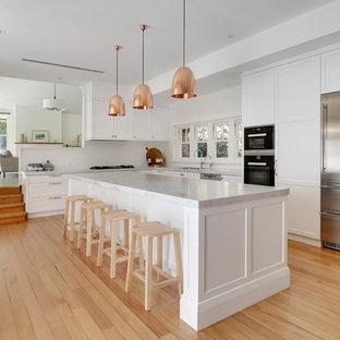 Große Klassische Wohnküche in L-Form mit Doppelwaschbecken, Schrankfronten im Shaker-Stil, weißen Schränken, Marmor-Arbeitsplatte, Küchenrückwand in Weiß, Rückwand aus Keramikfliesen, Küchengeräten aus Edelstahl, hellem Holzboden, Kücheninsel und gelbem Boden in Sydney