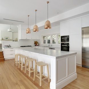 Photo of a large classic l-shaped kitchen/diner in Sydney with a double-bowl sink, shaker cabinets, white cabinets, marble worktops, white splashback, ceramic splashback, stainless steel appliances, light hardwood flooring, an island and yellow floors.