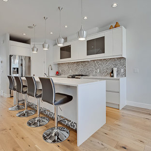 Mid-sized contemporary l-shaped kitchen pantry in Calgary with an undermount sink, flat-panel cabinets, grey cabinets, quartz benchtops, brown splashback, marble splashback, stainless steel appliances, light hardwood floors, with island, multi-coloured floor and white benchtop.