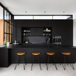 Design ideas for a kitchen in Melbourne with an undermount sink, flat-panel cabinets, black cabinets, black appliances, concrete floors, with island, grey floor and black benchtop.