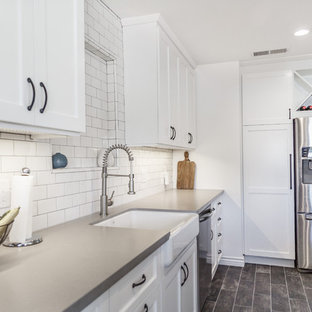 Design ideas for a mid-sized contemporary u-shaped separate kitchen in Orange County with a farmhouse sink, shaker cabinets, white cabinets, concrete benchtops, white splashback, subway tile splashback, stainless steel appliances, laminate floors, a peninsula, black floor and grey benchtop.