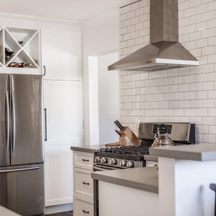 Inspiration for a mid-sized contemporary u-shaped separate kitchen in Orange County with a farmhouse sink, shaker cabinets, white cabinets, concrete benchtops, white splashback, subway tile splashback, stainless steel appliances, laminate floors, a peninsula, black floor and grey benchtop.