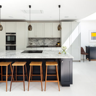 Design ideas for a mid-sized transitional galley open plan kitchen in London with an integrated sink, shaker cabinets, grey cabinets, grey splashback, panelled appliances, porcelain floors, with island, grey floor and black benchtop.