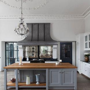 Foto på ett mycket stort vintage kök, med grå skåp, träbänkskiva, stänkskydd med metallisk yta, spegel som stänkskydd, mörkt trägolv, en köksö, luckor med profilerade fronter, svarta vitvaror och brunt golv