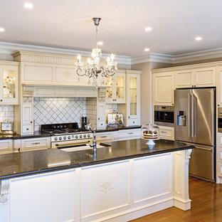 Неиссякаемый источник вдохновения для домашнего уюта: п-образная кухня среднего размера с обеденным столом, фасадами в стиле шейкер, желтыми фасадами, островом, раковиной в стиле кантри, столешницей терраццо, белым фартуком, фартуком из плитки кабанчик, белой техникой, паркетным полом среднего тона, коричневым полом и белой столешницей