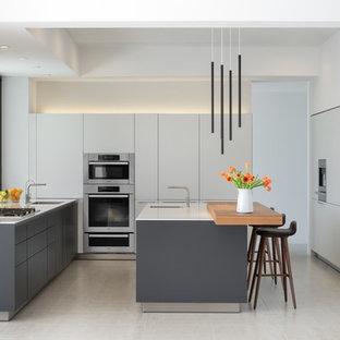 Стильный дизайн: отдельная, п-образная кухня среднего размера в современном стиле с плоскими фасадами, белыми фасадами, столешницей из кварцевого агломерата, полом из керамогранита, островом, белым фартуком, белым полом, фартуком из керамогранитной плитки, врезной раковиной, техникой под мебельный фасад и белой столешницей - последний тренд