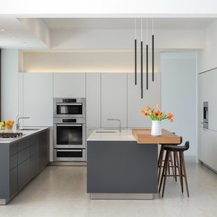Inredning av ett modernt mellanstort vit vitt u-kök, med släta luckor, vita skåp, bänkskiva i kvarts, klinkergolv i porslin, en köksö, vitt stänkskydd, vitt golv, stänkskydd i porslinskakel, en undermonterad diskho och integrerade vitvaror
