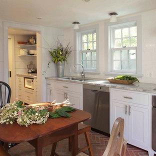 Exemple d'une cuisine américaine nature avec un évier 2 bacs, un placard à porte shaker, des portes de placard blanches, une crédence blanche, une crédence en carrelage métro, un électroménager en acier inoxydable, un plan de travail en marbre et un sol en brique.