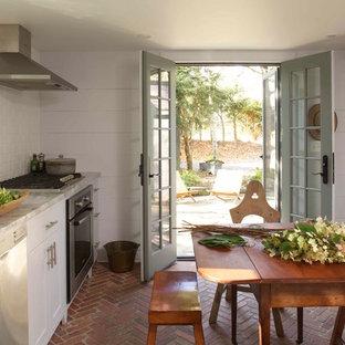 Foto de cocina de estilo de casa de campo con armarios estilo shaker, puertas de armario blancas, encimera de mármol, salpicadero blanco, salpicadero de azulejos tipo metro, electrodomésticos de acero inoxidable y suelo de ladrillo