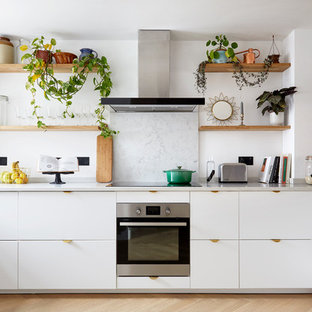 Inspiration for a scandinavian kitchen in London with a built-in sink, flat-panel cabinets, white cabinets, quartz worktops, stone slab splashback, stainless steel appliances, light hardwood flooring and grey worktops.