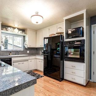 オースティンの中サイズのエクレクティックスタイルのおしゃれなキッチン (ダブルシンク、フラットパネル扉のキャビネット、白いキャビネット、御影石カウンター、グレーのキッチンパネル、黒い調理設備、ラミネートの床、ベージュの床、グレーのキッチンカウンター) の写真