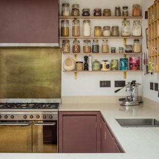 Réalisation d'une petit cuisine américaine design en U avec un évier posé, un placard à porte plane, des portes de placard violettes, un plan de travail en quartz modifié, un électroménager noir et un sol en liège.