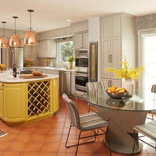 ミネアポリスのエクレクティックスタイルのおしゃれなキッチン (アンダーカウンターシンク、レイズドパネル扉のキャビネット、ベージュのキャビネット、ベージュキッチンパネル、シルバーの調理設備、テラコッタタイルの床、オレンジの床、白いキッチンカウンター) の写真