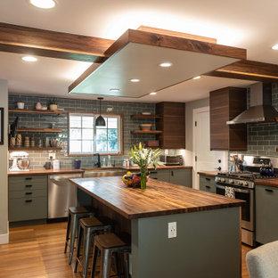 デンバーのラスティックスタイルのおしゃれなキッチン (エプロンフロントシンク、フラットパネル扉のキャビネット、緑のキャビネット、木材カウンター、グレーのキッチンパネル、サブウェイタイルのキッチンパネル、シルバーの調理設備、無垢フローリング、茶色い床、茶色いキッチンカウンター) の写真
