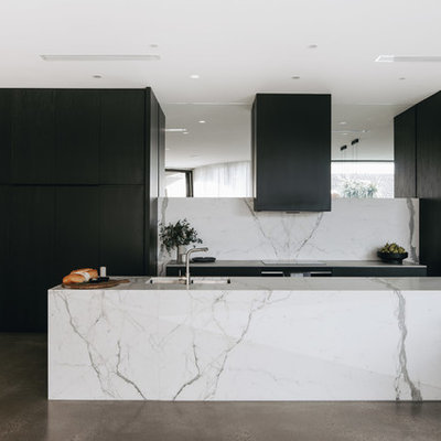 Eat-in kitchen - contemporary galley concrete floor and gray floor eat-in kitchen idea in Adelaide with an undermount sink, flat-panel cabinets, black cabinets, white backsplash, paneled appliances, an island and white countertops