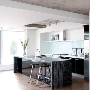 Ispirazione per una cucina moderna di medie dimensioni con elettrodomestici in acciaio inossidabile, lavello sottopiano, ante lisce, ante nere, paraspruzzi bianco, paraspruzzi in lastra di pietra, parquet chiaro, isola e pavimento beige