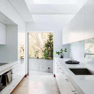 This is an example of a large midcentury galley separate kitchen in Sydney with an undermount sink, quartz benchtops, white splashback, glass sheet splashback, black appliances, travertine floors, white benchtop, flat-panel cabinets, white cabinets, no island and beige floor.