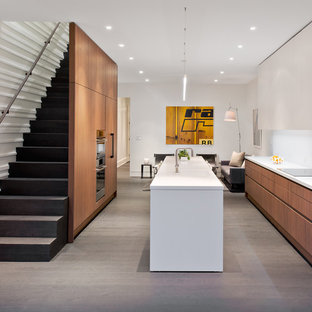 Mid-sized contemporary l-shaped open plan kitchen in DC Metro with an integrated sink, flat-panel cabinets, quartz benchtops, white splashback, panelled appliances, with island, medium wood cabinets, medium hardwood floors, stone slab splashback and grey floor.