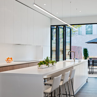 Photo of a mid-sized contemporary l-shaped eat-in kitchen in DC Metro with an integrated sink, flat-panel cabinets, white cabinets, quartz benchtops, white splashback, with island, panelled appliances, medium hardwood floors and white benchtop.