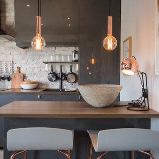 Foto de cocina contemporánea, pequeña, con armarios con paneles lisos, puertas de armario grises, salpicadero de ladrillos, península, encimeras marrones, fregadero encastrado, encimera de madera y electrodomésticos negros