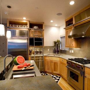 ソルトレイクシティの中くらいのインダストリアルスタイルのおしゃれなキッチン (アンダーカウンターシンク、シェーカースタイル扉のキャビネット、中間色木目調キャビネット、メタリックのキッチンパネル、シルバーの調理設備、淡色無垢フローリング、茶色い床) の写真