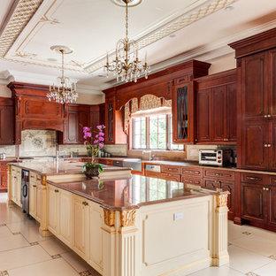 Geräumige, Geschlossene Klassische Küche in U-Form mit Landhausspüle, profilierten Schrankfronten, dunklen Holzschränken, Granit-Arbeitsplatte, Küchenrückwand in Beige, Rückwand aus Keramikfliesen, Elektrogeräten mit Frontblende, Keramikboden, zwei Kücheninseln, beigem Boden und brauner Arbeitsplatte in New York