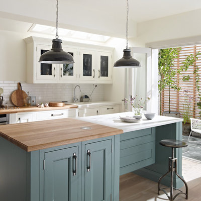 Kitchen - traditional light wood floor kitchen idea in London with recessed-panel cabinets, white cabinets, white backsplash, subway tile backsplash, stainless steel appliances and an island