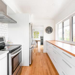 他の地域の小さい北欧スタイルのおしゃれなキッチン (アンダーカウンターシンク、フラットパネル扉のキャビネット、白いキャビネット、木材カウンター、白いキッチンパネル、磁器タイルのキッチンパネル、シルバーの調理設備、無垢フローリング、アイランドなし、茶色い床、マルチカラーのキッチンカウンター) の写真