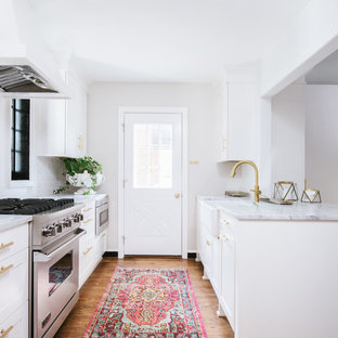 Small transitional kitchen ideas - Inspiration for a small transitional galley medium tone wood floor and brown floor kitchen remodel in DC Metro with a farmhouse sink, shaker cabinets, white cabinets, marble countertops, white backsplash, ceramic backsplash, stainless steel appliances and a peninsula