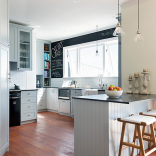This is an example of a transitional u-shaped kitchen in Sydney with a farmhouse sink, shaker cabinets, grey cabinets, white splashback, subway tile splashback, black appliances, dark hardwood floors, a peninsula, brown floor and black benchtop.