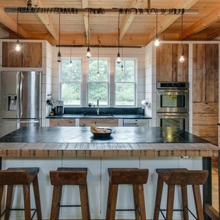 Farmhouse kitchen ideas - Farmhouse light wood floor and beige floor kitchen photo in Nashville with a double-bowl sink, medium tone wood cabinets, stainless steel appliances, an island and black countertops