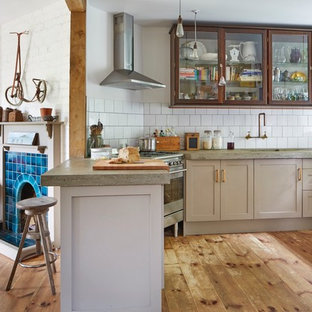 Eclectic eat-in kitchen designs - Eclectic light wood floor eat-in kitchen photo in Devon with a farmhouse sink, shaker cabinets, brown cabinets, concrete countertops and subway tile backsplash