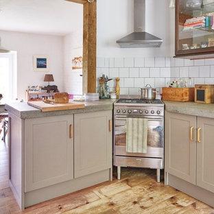 デヴォンのエクレクティックスタイルのおしゃれなダイニングキッチン (エプロンフロントシンク、シェーカースタイル扉のキャビネット、茶色いキャビネット、コンクリートカウンター、サブウェイタイルのキッチンパネル、淡色無垢フローリング) の写真
