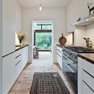 Modelo de cocina de galera, contemporánea, de tamaño medio, cerrada, con armarios con paneles lisos, puertas de armario blancas, electrodomésticos de acero inoxidable, suelo de madera clara, fregadero encastrado, encimera de madera y salpicadero blanco