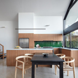 Mid-sized contemporary l-shaped open plan kitchen in Melbourne with a double-bowl sink, flat-panel cabinets, medium wood cabinets, green splashback, glass tile splashback, stainless steel appliances, with island, grey floor and white benchtop.